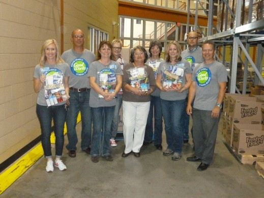 Martin Pringle GoodWorks volunteers show off the food they assembled for the Food-4-Kids program at the Kansas Food Bank.